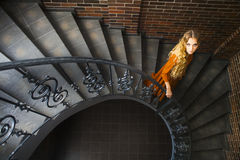 Blond woman in long dress on the stairs Stock Image