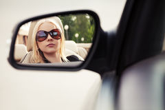 Blond woman looking in the car rear view mirror Royalty Free Stock Images
