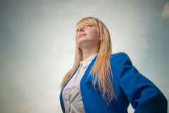 Blond woman looking into future. Successful Business woman, blond in white shirt and blue jacket looking into future on cloudy sky background Stock Photos