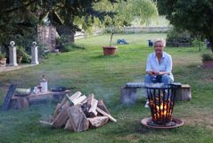 Blond woman looks at the campfire in the fire basket royalty free stock images