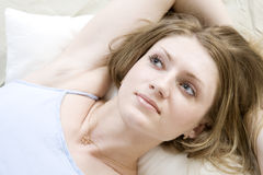 Blond woman lying on bed Royalty Free Stock Image