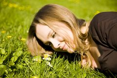 Blond woman lying on grass stock photo