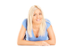 Blond woman lying on ground and looking at camera Royalty Free Stock Images