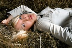 Blond woman lying on haystack Stock Photos