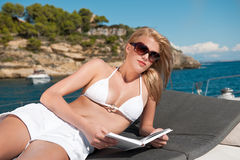 Blond woman lying on yacht reading book Stock Image