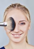 Closeup of woman's face and makeup brush Royalty Free Stock Images