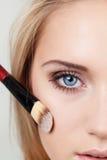 Closeup of woman with makeup brush Stock Images