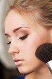 Closeup of woman's face and makeup brush royalty free stock photos