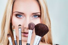 Closeup of woman's face and makeup brushes Royalty Free Stock Photography