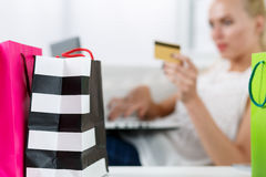 Blond woman making purchasing via internet paying credit card. Focus on fresh buyings packed in colored paper bags standing in front of her. Shopping Stock Photography