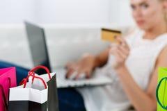 Blond woman making purchasing via internet paying credit card Stock Photo