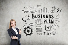 Blond woman with a marker near a business plan sketch on a concr Stock Image