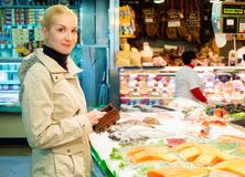 Blond woman on market. Young blond woman buying fish on market Royalty Free Stock Images