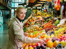Blond woman on market. Young cheerful blond woman choosing fresh fruits on market Royalty Free Stock Photo