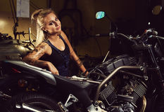 Blond woman mechanic. In a motorcycle workshop royalty free stock images