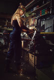 Blond woman mechanic. Woman mechanic working in a motorcycle workshop stock photo