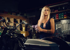Blond woman mechanic in a workshop. Blond woman mechanic in a motorcycle workshop Royalty Free Stock Image