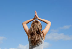 Blond woman meditating against a blue sky Stock Photography