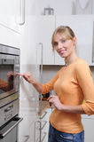 Blond woman with a microwave Stock Photos
