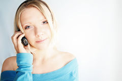 Blond woman with mobile. Portrait of young blond haired woman with mobile telephone, white studio background Stock Images