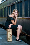 Blond woman near an old train. Blond woman sitting on a suitcase near an old train Royalty Free Stock Photos