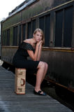 Blond woman near an old train. Blond woman sitting on a suitcase near an old train Stock Photos