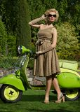 Blond woman near scooter Royalty Free Stock Photos