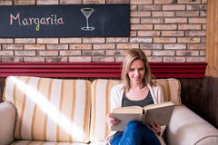 Blond woman with newspaper in cafe drinking coffee Stock Photography