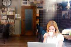 Blond woman with notebook in cafe drinking coffee Stock Photos
