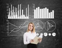 Blond woman with a notebook and four graphs on a chalkboard Stock Image