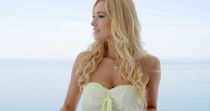 Blond Woman on Ocean Front Balcony Looking to Side stock video footage