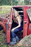 Blond woman in old truck. A pretty blond woman sitting in an old abandoned truck Stock Photo