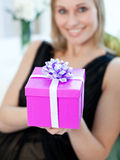 Blond woman opening a gift sitting on a sofa Stock Image