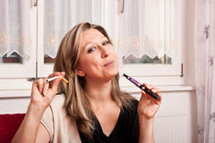 Blond woman opts for electronic cigarette Stock Image