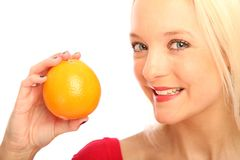 Blond woman with a orange. Young blond woman showing a orange stock image