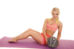 Blond woman orange fitness sit hold medicine ball twist Stock Photo