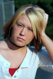 Blond Woman Outdoor Portrait. Outdoor portrait of a serious young woman, leaning her head against her hand Stock Photo
