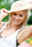 Blond woman outdoor. Young sexy blond woman outdoor in a garden with wet hair wearing summer hat Royalty Free Stock Photography