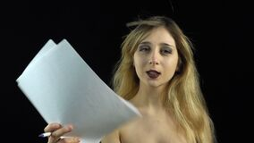 Blond woman with paper sheets. Footage of blond girl with bared shoulders on black background stock footage