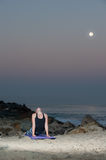 Blond woman in pattern tights performing back extension at night. Royalty Free Stock Photography