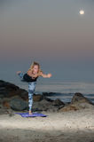 Blond woman in pattern tights performing lengthening stretch at night. Stock Images