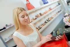 Blond woman paying for shoes in shop. Blond woman paying for shoes in a shop Royalty Free Stock Photography