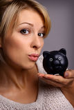 blond woman and piggy bank Stock Images