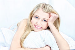 Blond woman on pillow. Cute blond woman on pillow in bedroom Royalty Free Stock Photo