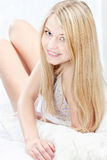 Blond woman on pillow in bedroom Stock Image