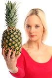 Blond woman with a Pineapple. Young blond woman showing a Pineapple stock images