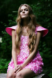 Blond woman in pink dress in forest. Blond woman in pink dress in deep dark forest Royalty Free Stock Photography