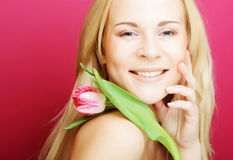 Blond woman with pink tulip Stock Images
