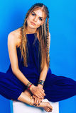 Blond woman with plaits in blue overall Stock Image