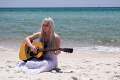 Blond Woman Playing Spruce Top Dreadnought Acoustic Guitar by the Seashore Stock Photo